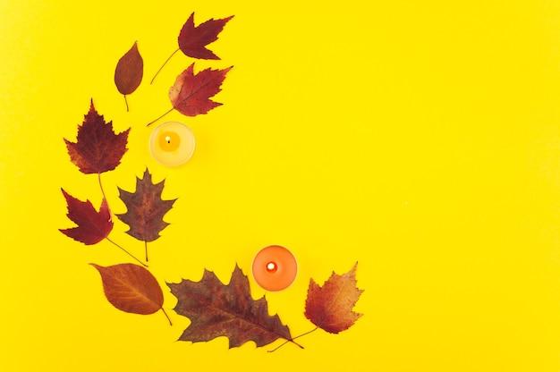 Coroa de flores com folhas de carvalho e bordo multicoloridas em plano de fundo amarelo leigo. outono colorido com velas acesas em laranja e vermelho