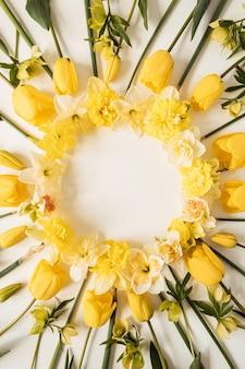 Coroa de flores com moldura redonda feita de narciso amarelo e flores de tulipa em branco