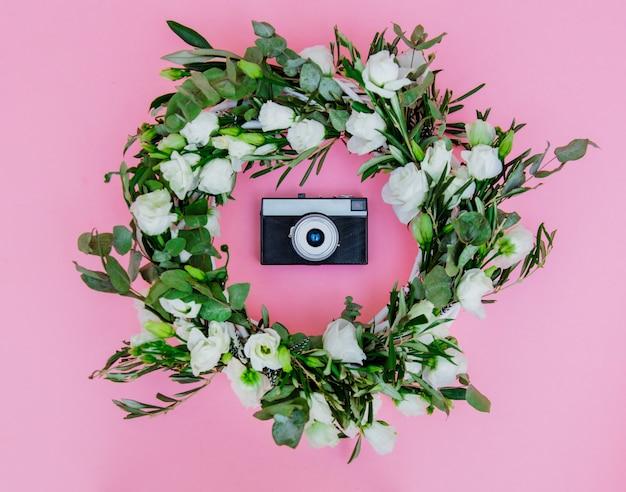 Coroa de flores com rosas brancas e câmera vintage em fundo branco. decorado