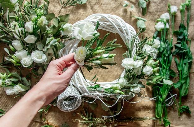 Coroa de flores com rosas brancas em fundo de juta. decorado