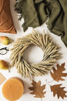Coroa de flores feita de palha de trigo, cobertor, travesseiro, copos, peras, envolvente, folhas secas de outono e vela em branco. camada plana, vista superior