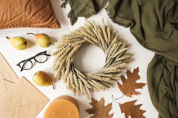 Coroa de flores feita de palha de trigo na mesa branca com cobertor, travesseiro, copos, peras, envelopes, folhas secas de outono e vela. camada plana, vista superior