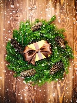 Coroa de flores na placa de madeira. caixa de presente embrulhada. natal