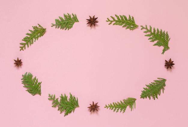 Coroa de galhos de pinheiro e anis estrelado em um fundo rosa, fundo de férias de natal, camada plana
