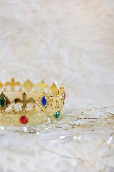 Coroa de ouro com gemas coloridas e ornamentos de ouro sobre fundo branco de pano. vertical.