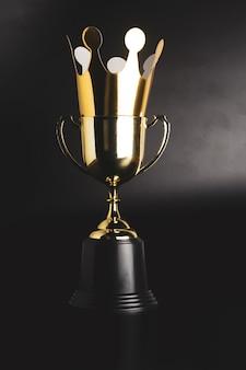 Coroa de ouro de papelão em cima do troféu de ouro campeão.
