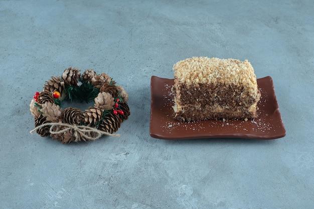 Coroa de pinha ao lado de um prato com uma fatia de bolo na superfície de mármore