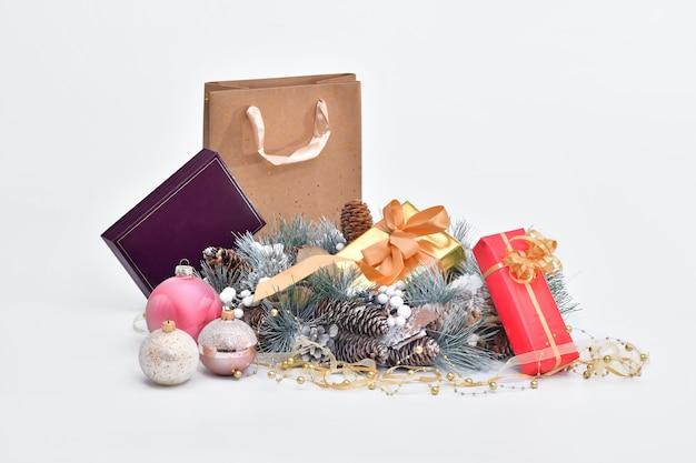 Coroa de pinha cercada por caixas de presente embrulhadas e enfeites de natal