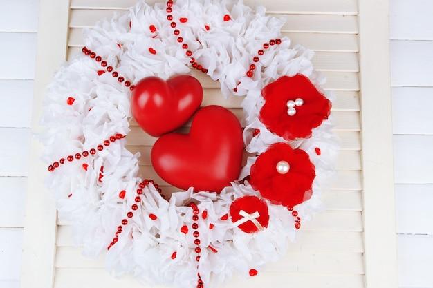 Coroa decorativa com corações na superfície de madeira