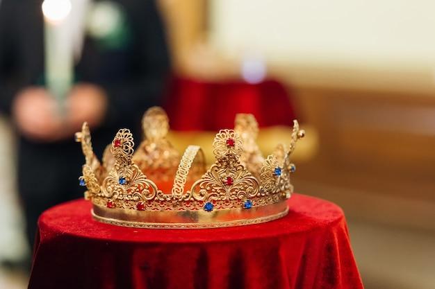 Coroa dourada com pedras preciosas na toalha de mesa vermelha na tradicional cerimônia de casamento da igreja
