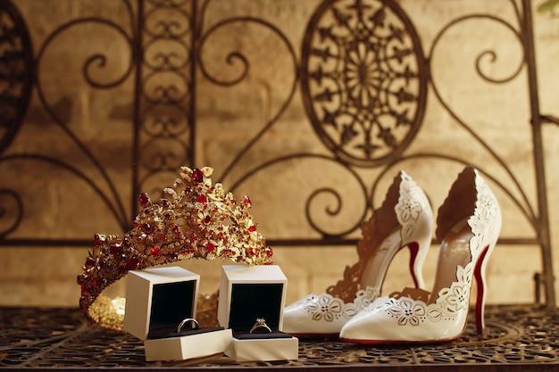 Coroa dourada com pedras vermelhas, anéis de casamento