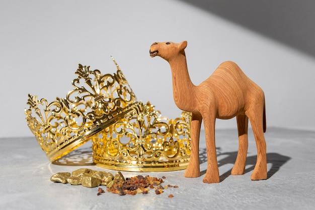 Coroas de ouro do dia da epifania com estatueta de camelo e passas
