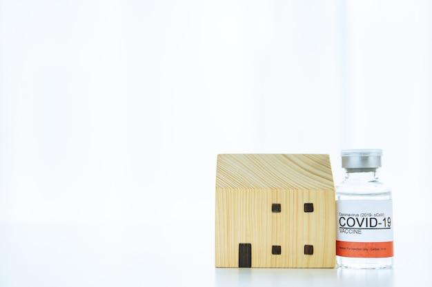 Coronavirus, 2019-ncov ou covid-19 vacina e seringa injetável com modelo caseiro de madeira, um conceito de cuidar da saúde e proteger a família de covid-19 com copyspace.