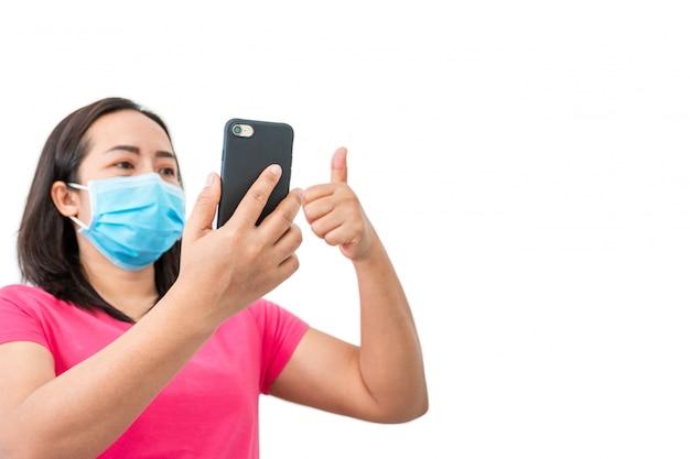 Coronavírus covid-19, durante a detenção em casa mulheres mascaradas usam telefones para fazer chamadas de vídeo para amigos.
