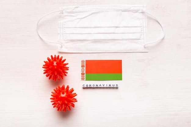 Coronavírus covid conceito vista superior máscara protetora de respiração e bandeira da bielorrússia