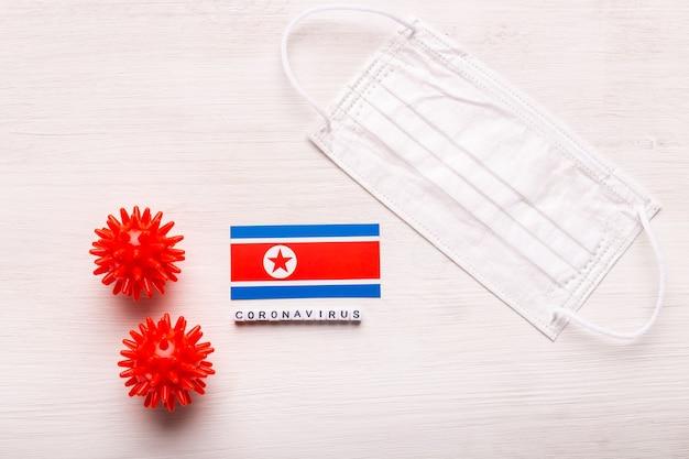 Coronavírus covid conceito vista superior máscara protetora de respiração e bandeira da coreia do norte