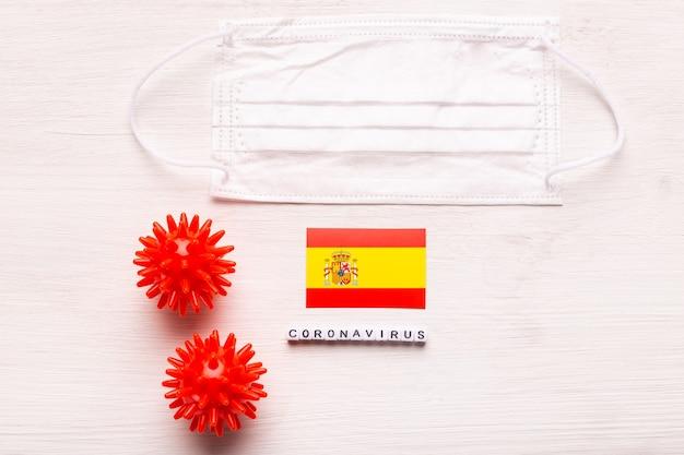 Coronavirus covid conceito vista superior máscara protetora de respiração e bandeira da espanha