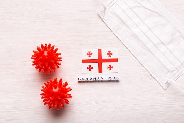 Coronavirus covid conceito vista superior máscara protetora de respiração e bandeira da geórgia