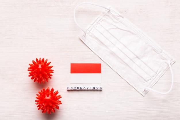 Coronavírus covid conceito vista superior máscara protetora de respiração e bandeira da indonésia