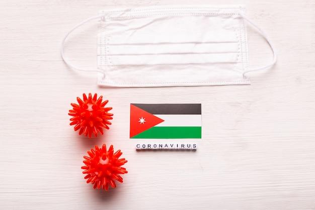 Coronavirus covid conceito vista superior máscara protetora de respiração e bandeira da jordânia