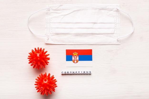 Coronavirus covid conceito vista superior máscara protetora de respiração e bandeira da sérvia