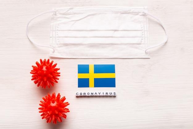 Coronavírus covid conceito vista superior máscara protetora de respiração e bandeira da suécia