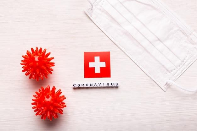 Coronavirus covid conceito vista superior máscara protetora de respiração e bandeira da suíça