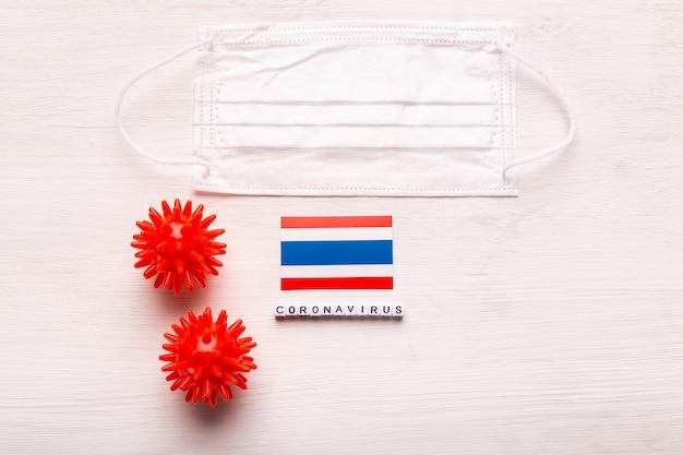 Coronavirus covid conceito vista superior máscara protetora de respiração e bandeira da tailândia