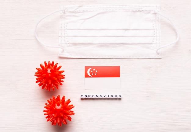 Coronavírus covid conceito vista superior máscara protetora de respiração e bandeira de singapura