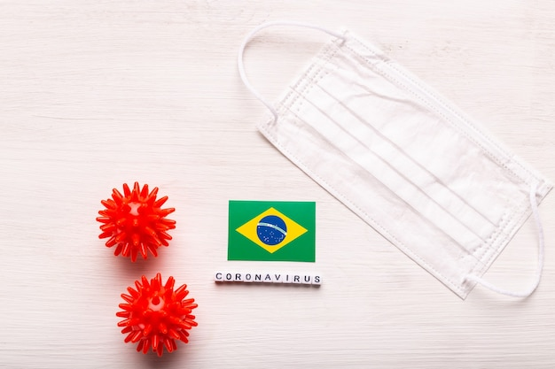 Coronavirus covid conceito vista superior máscara protetora de respiração e bandeira do brasil