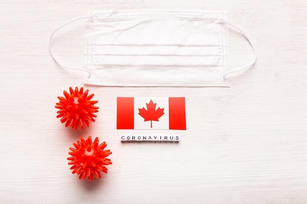 Coronavirus covid conceito vista superior máscara protetora de respiração e bandeira do canadá