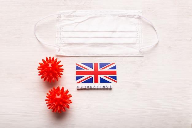 Coronavirus covid conceito vista superior máscara protetora de respiração e bandeira do reino unido