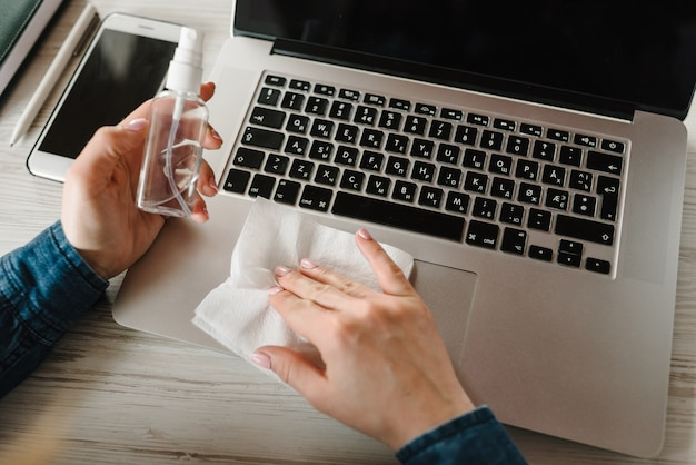 Coronavírus. desinfetante. mulher que trabalha em quarentena. limpeza de mãos telefone móvel, computador portátil para eliminar germes spray antibacteriano. ficar em casa. impedir o vírus covid-19. desinfecção de toalhetes.