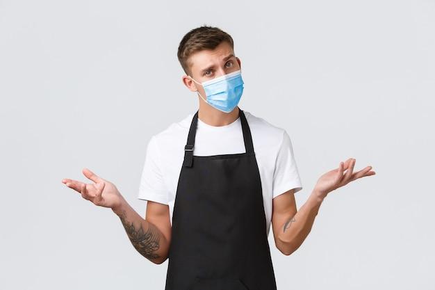 Coronavírus, distanciamento social em cafés e restaurantes, negócios durante o conceito de pandemia. barista bonito confuso, vendedor com máscara médica encolhendo os ombros, parecendo um fundo branco indeciso