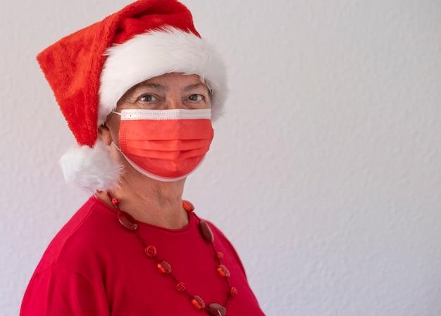 Coronavírus e natal de 2020. retrato de uma mulher sênior com chapéu de papai noel usando máscara cirúrgica devido ao coronavírus, olhando para a câmera. cor vermelha em fundo branco