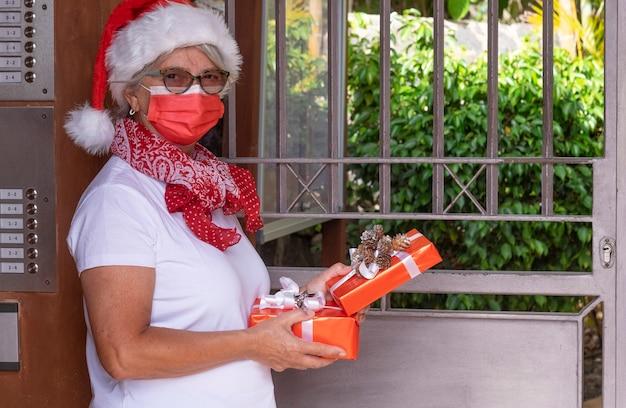 Coronavírus e o natal de 2020. uma mensageira sênior usando um chapéu de papai noel e uma máscara médica para evitar a infecção por coronavírus entregando presentes de natal em casa