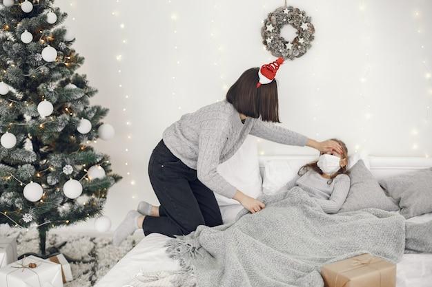 Coronavírus em criança. mãe com filha. criança deitada em uma cama. mulher com uma máscara médica.