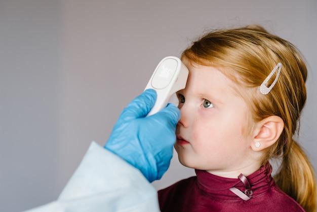 Coronavírus. enfermeira, médico verifica a temperatura corporal da garota usando o termômetro infravermelho da testa (arma) para detectar o sintoma do vírus - conceito de epidemia. temperatura alta.