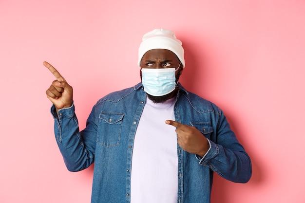 Coronavírus, estilo de vida e conceito de pandemia global. cara afro-americano confuso e desapontado com máscara facial apontando o dedo para a esquerda, olhando chateado com a câmera, fundo rosa
