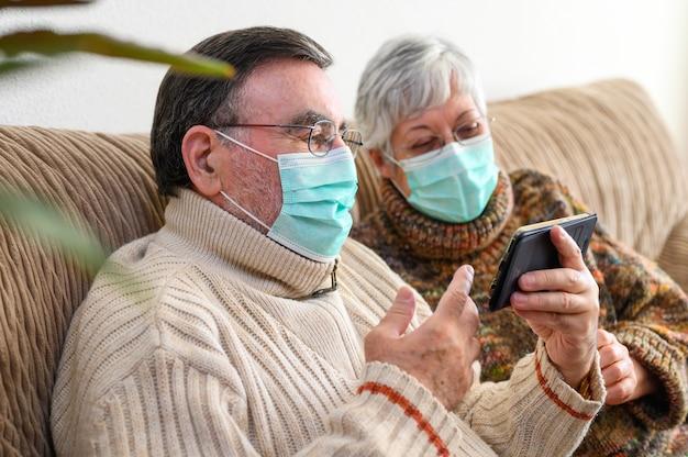 Coronavírus. fique em casa, estilo de vida. casal de idosos alegres sentado em um sofá em quarentena em casa, fazendo uma vídeo chamada com o smartphone. casal sênior usando máscaras de proteção.