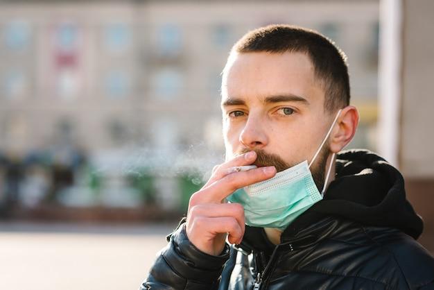Coronavírus. fumar. homem do close up com máscara durante a pandemia de covid-19 que fuma um cigarro na rua. fumar causa câncer de pulmão e outras doenças