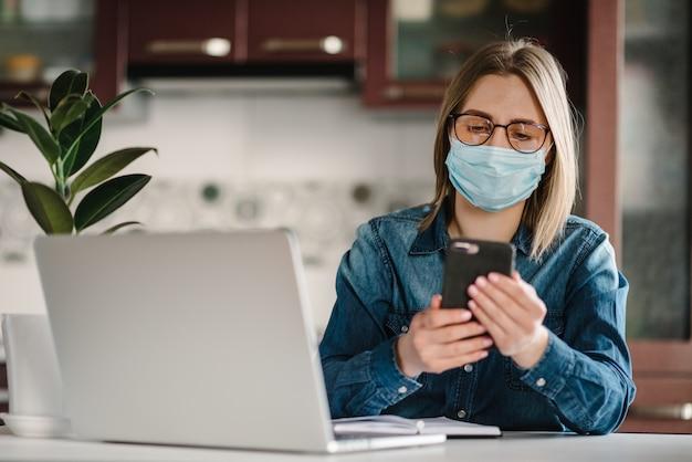 Coronavírus. garota na máscara de verificação de aplicativos sociais no telefone. mulher trabalha, aprende e usando o computador portátil. quarentena. ficar em casa. trabalhador autonomo. escrevendo, digitando. conceito de comunicação e tecnologia.