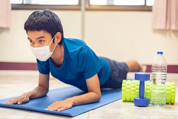 Coronavírus, homem asiático usa uma máscara e se exercita sozinho no quarto em casa para prevenir o covid-19. treino em casa, exercício em casa.