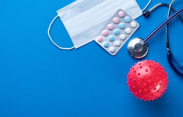 Coronavírus, máscaras descartáveis médicas protetoras, comprimidos e medicamentos, estetoscópio sobre um fundo azul.