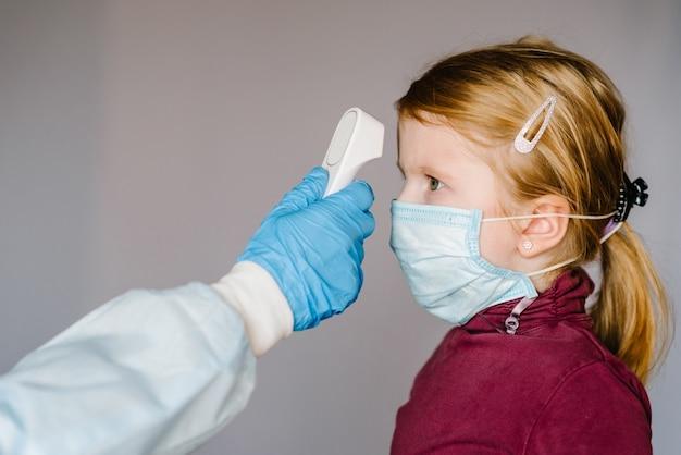 Coronavírus. médico verifica a temperatura do corpo da garota usando termômetro infravermelho na testa (arma) para detectar o sintoma do vírus - conceito de epidemia. temperatura alta.