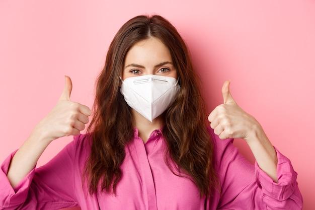 Coronavírus, medidas preventivas e conceito de saúde. perto de uma jovem alegre usa respirador de covid-19, mostra os polegares em aprovação, parede rosa.