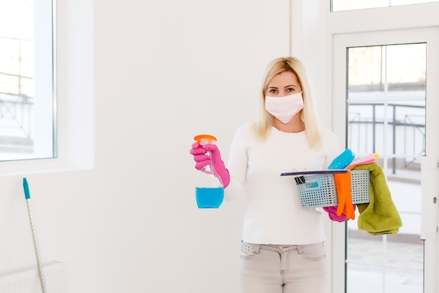 Coronavírus. mulher com máscara facial, limpando e desinfetando a casa dela durante a epidemia de coronavírus. prevenção da infecção por covid-19. impedir que o coronavírus se espalhe.