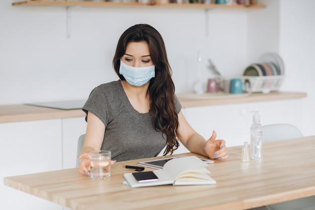 Coronavírus. mulher de negócios jovem trabalhando em casa usando máscara protetora. garota em quarentena por coronavírus usando máscara protetora. trabalhar em casa com gel desinfetante e água