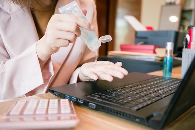 Coronavírus. mulher de negócios, trabalhando em casa. trabalhando em casa. limpando as mãos com gel desinfetante.