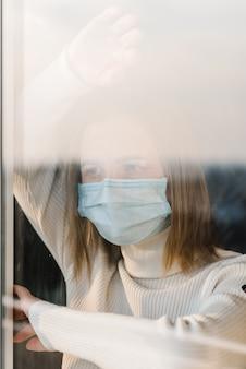 Coronavírus. mulher doente usando máscara de proteção, olhando pela janela e recuperação da doença em casa